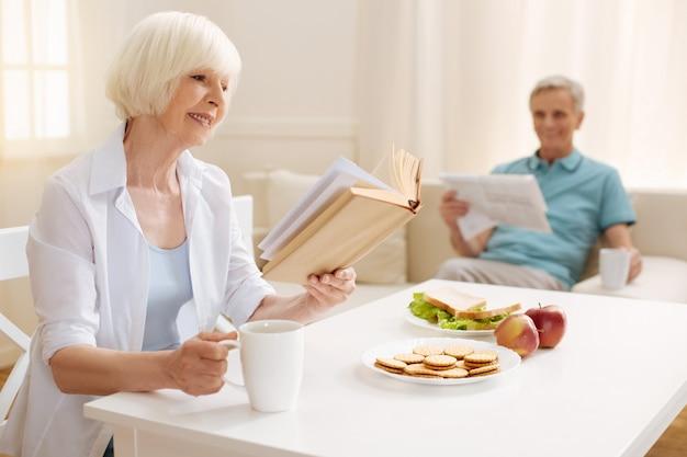 Mulher bonita vibrante e imaginativa lendo um livro fascinante que não desiste, mesmo quando está tomando o café da manhã
