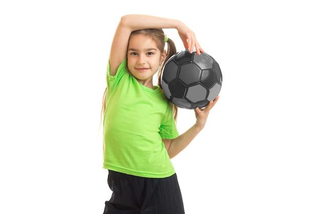 Mulher bonitinha com uma bola de futebol nas mãos isolado no branco