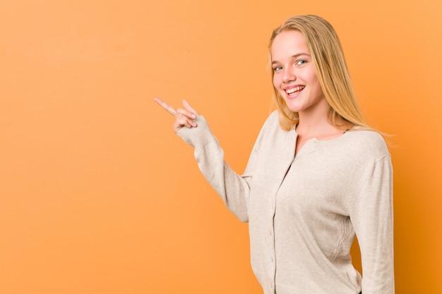 Mulher bonito e natural adolescente sorrindo alegremente apontando com o dedo indicador fora.