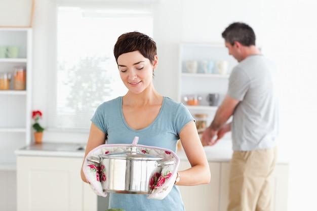 Mulher bonito segurando uma panela enquanto o homem está lavando a louça