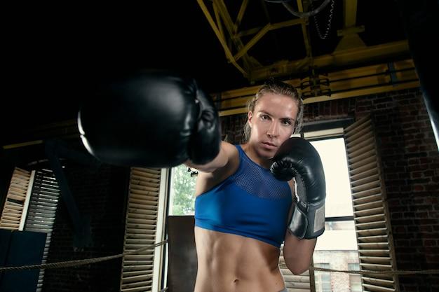 Mulher boxeadora jogando a mão para frente