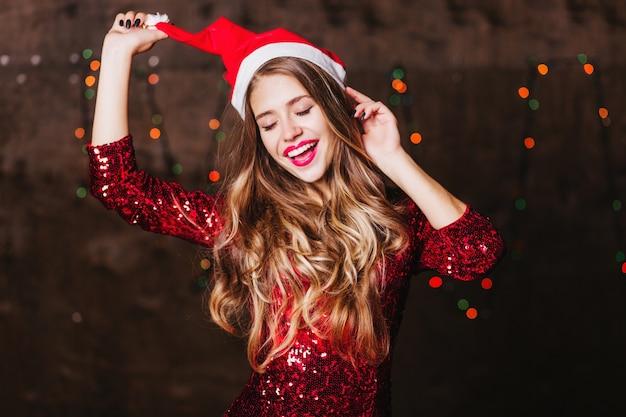 Mulher branca alegre com cabelo longo e brilhante posando com chapéu de papai noel