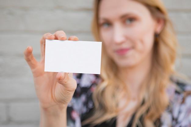 Mulher branca alegre mostrando seu cartão de visita