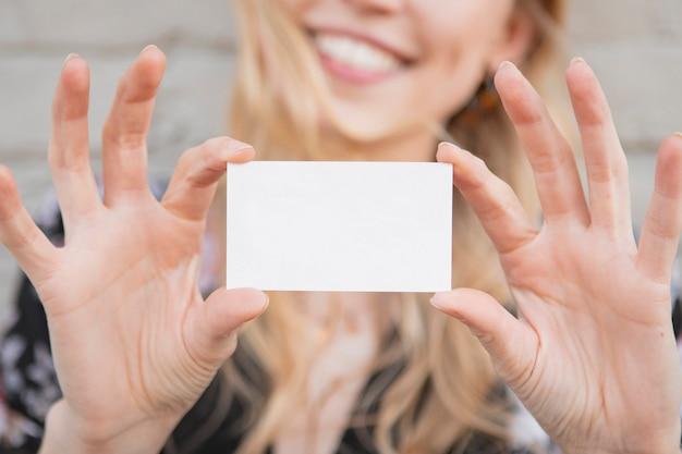 Mulher branca alegre mostrando um cartão vazio