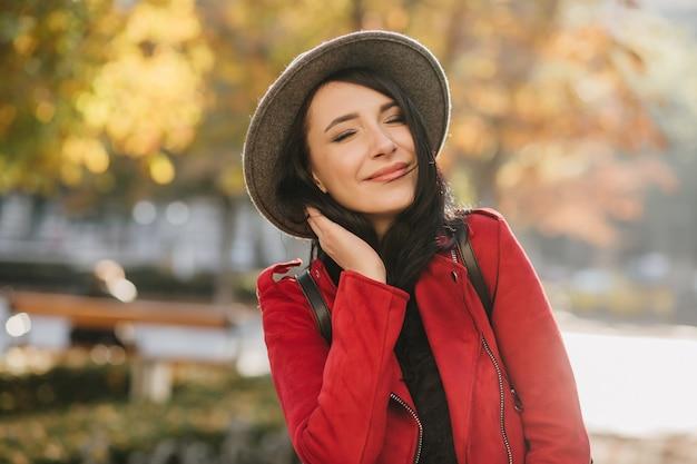 Mulher branca alegre vestida de vermelho curtindo o outono