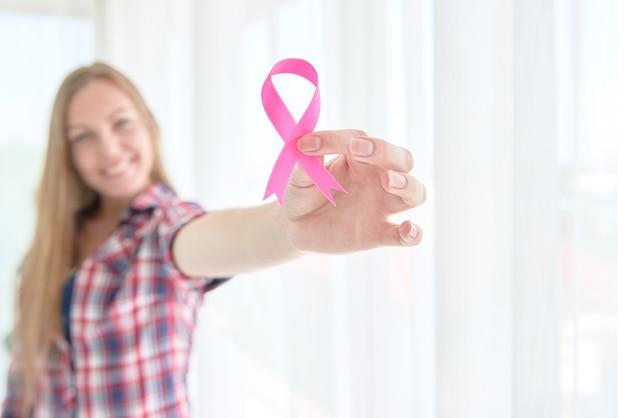Mulher branca branca segurando fita rosa conscientização do câncer de mama para o conceito de campanha do mês de conscientização do câncer de mama.