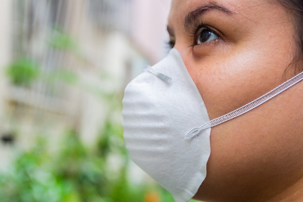Mulher branca com máscara no rosto para se proteger do coronavírus.