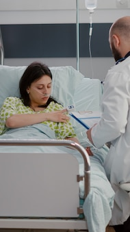 Mulher branca com tubo de oxigênio nasal, sentada na cama na enfermaria do hospital