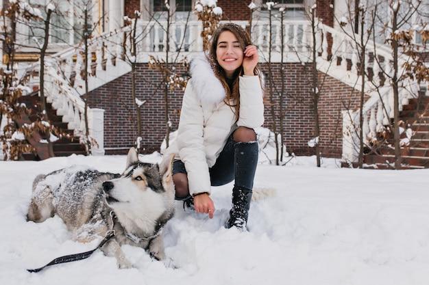Mulher branca com um sorriso incrível, posando com seu cachorro durante o inverno andar no quintal. foto ao ar livre de senhora alegre usa calças jeans rasgadas, sentado na neve com husky preguiçoso.