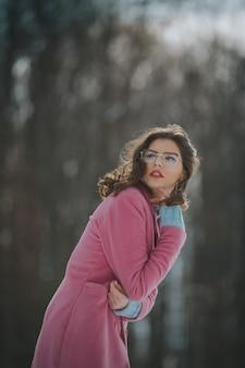 Mulher branca com uma jaqueta quente rosa brilhante em uma floresta de neve no inverno