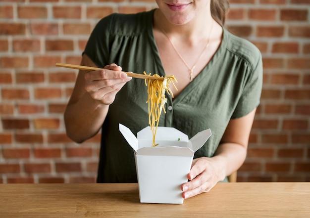Mulher branca comendo chow mein