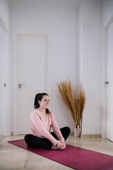 Mulher branca de cabelos escuros fazendo alongamentos de ioga em casa devido à quarentena