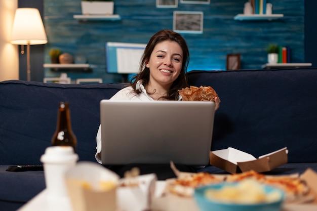 Mulher branca descansando no sofá, olhando para a câmera, comendo hambúrguer saboroso enquanto trabalhava no laptop