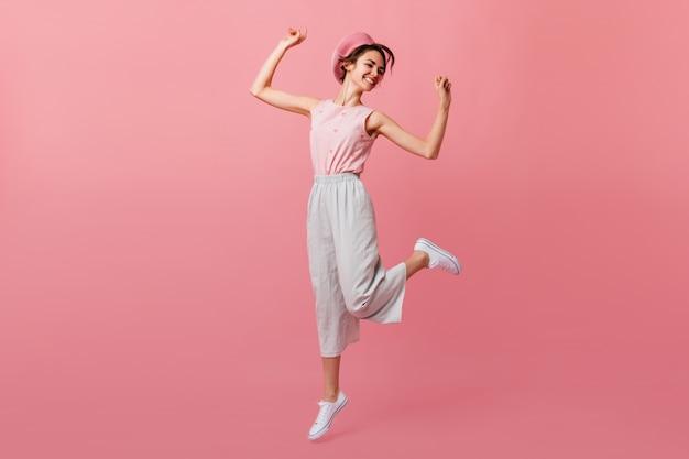 Mulher branca despreocupada dançando com as mãos para cima