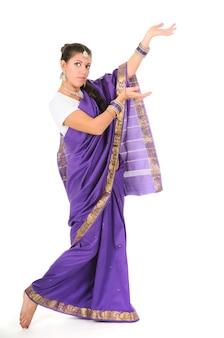 Mulher branca e sorridente em pé, posando com roupas tradicionais indianas roxas. energia de dança. retrato isolado em fundo branco