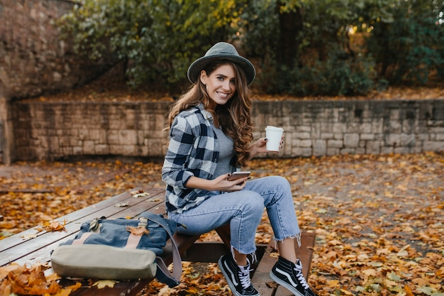 Mulher branca em êxtase em jeans vintage, sentada em um banco de madeira em dia de outono