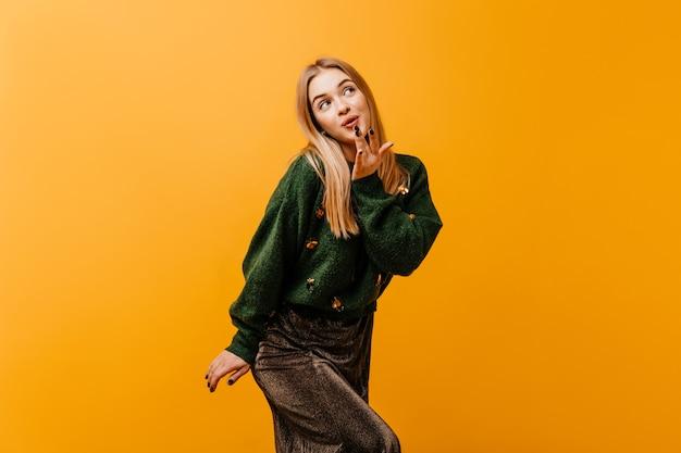 Mulher branca em êxtase posando divertidamente em laranja. retrato interior de inspirada mulher caucasiana, se divertindo no estúdio.