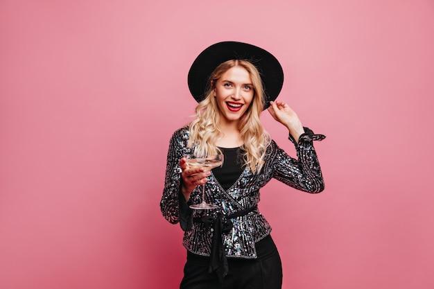 Mulher branca encantadora posando com um copo de vinho na parede pastel. foto interna de uma menina loira bem-humorada de chapéu preto.