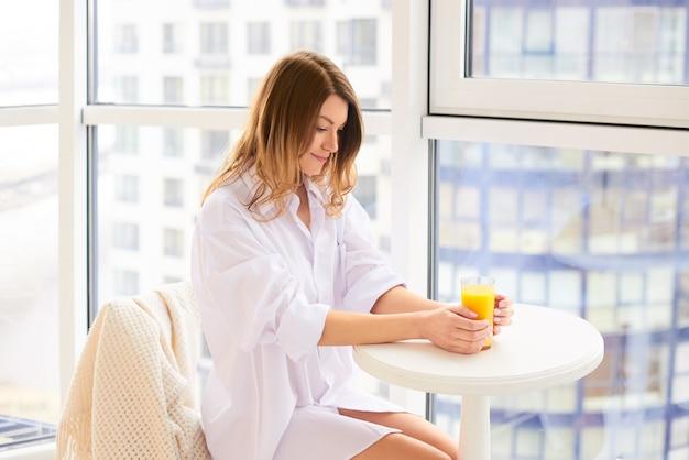 Mulher branca feliz em casa bebendo suco de laranja fresco na manhã na cozinha