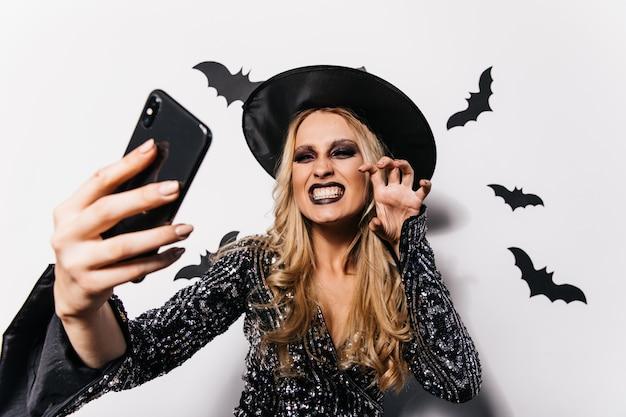 Mulher branca feliz posando com fantasia de feiticeiro. foto interna de menina loira positiva fazendo selfie com morcegos de halloween na parede.