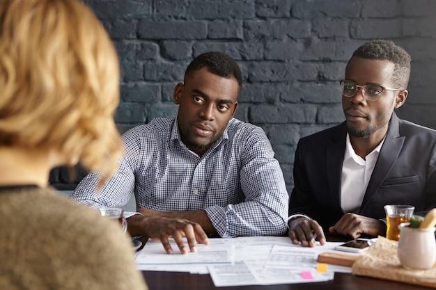 Mulher branca irreconhecível sendo entrevistada por um futuro chefe duvidoso e diretor de rh