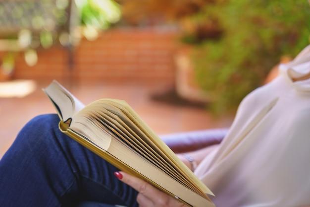 Mulher branca lendo um livro em uma poltrona relaxante à luz do dia lá fora.