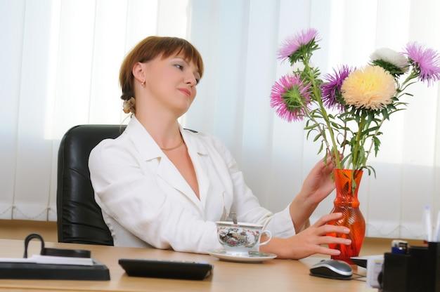 Mulher branca morena branca se senta à mesa abraçando o buquê de flores. copo, mouse de computador, pasta de documentos na mesa.