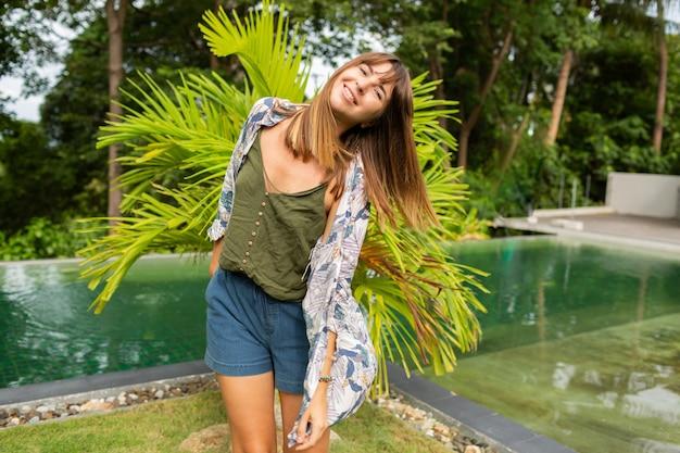 Mulher branca natural posando perto de piscina e palmeiras.
