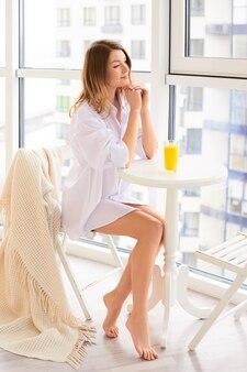 Mulher branca pensativa em casa bebendo suco de laranja fresco na manhã na sala de estar