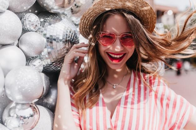Mulher branca romântica com longos cabelos loiros rindo perto de bolas de brilho. adorável garota caucasiana com chapéu de palha e óculos de sol rosa, aproveitando o verão.