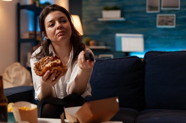 Mulher branca segurando um hambúrguer saboroso nas mãos, mudando de canal usando controle remoto, assistindo a uma série de comédia