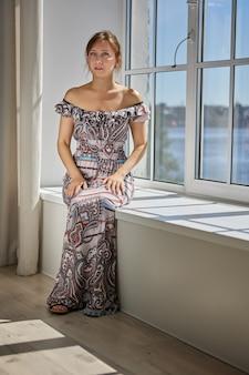 Mulher branca sensual de anos sentada no parapeito da janela