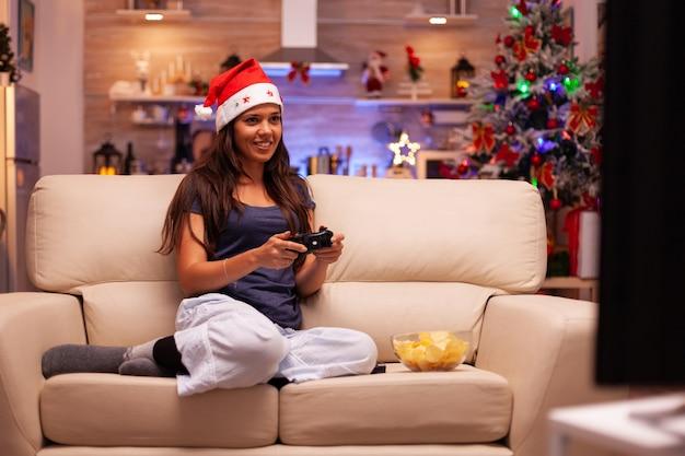 Mulher branca sentada no sofá jogando videogame on-line usando o joystick de jogo