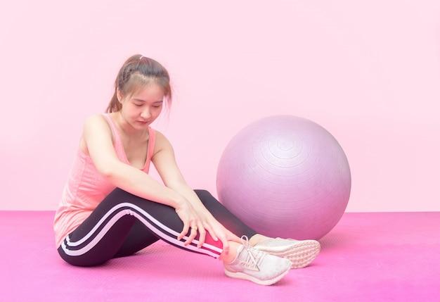 Mulher branca, tendo dor no tornozelo enquanto treino na academia.
