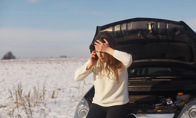 Mulher branca tendo um problema com o carro em uma viagem