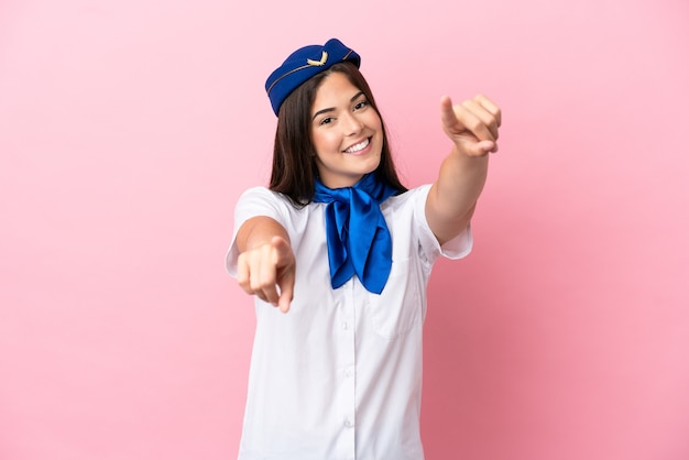 Mulher brasileira com aeromoça de avião isolada em um fundo rosa apontando o dedo para você enquanto sorri