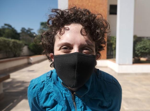 Mulher brasileira de cabelo encaracolado usando máscara em um dia ensolarado.