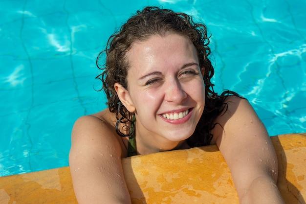 Mulher brasileira de cabelos cacheados relaxando na piscina olhando para a câmera.