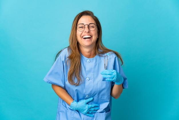 Mulher brasileira de meia-idade dentista segurando ferramentas isoladas