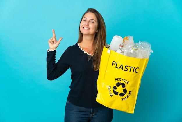 Mulher brasileira de meia-idade segurando uma sacola cheia de garrafas plásticas para reciclar