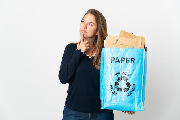 Mulher brasileira de meia-idade segurando uma sacola de reciclagem cheia de papel para reciclar sobre um fundo isolado com dúvidas enquanto olha para cima
