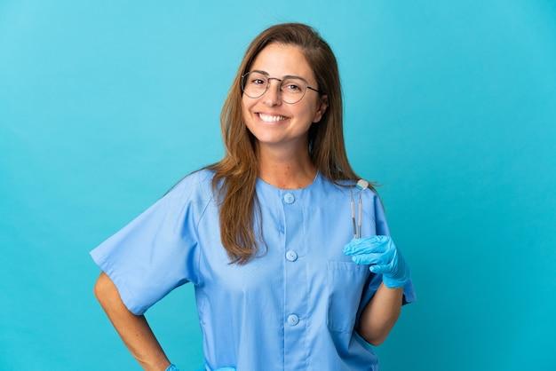 Mulher brasileira, dentista de meia-idade, segurando ferramentas isolada