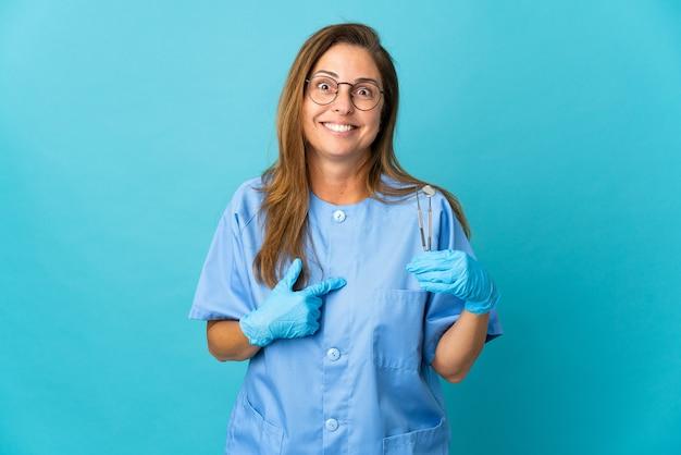 Mulher brasileira, dentista de meia-idade, segurando ferramentas sobre uma parede isolada com expressão facial surpresa