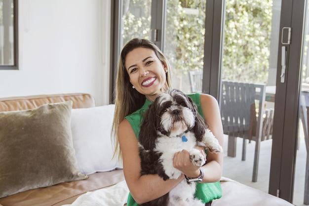 Mulher brasileira e seu cachorro shih tzu de estimação em casa, melhor amiga, amor familiar