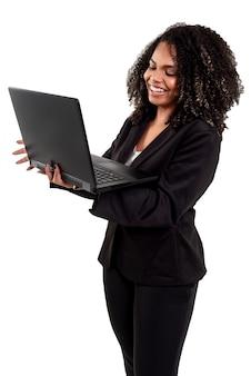 Mulher brasileira negra executiva alegre e sorridente isolada no branco, trabalhando com um notebook.