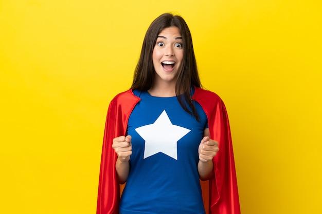 Mulher brasileira super-heroína isolada em fundo amarelo comemorando vitória na posição de vencedora