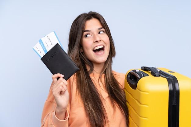 Mulher brasileira viajante segurando uma mala e um passaporte