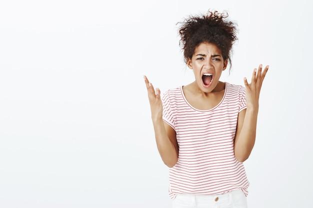 Mulher brava descontente com penteado afro posando no estúdio
