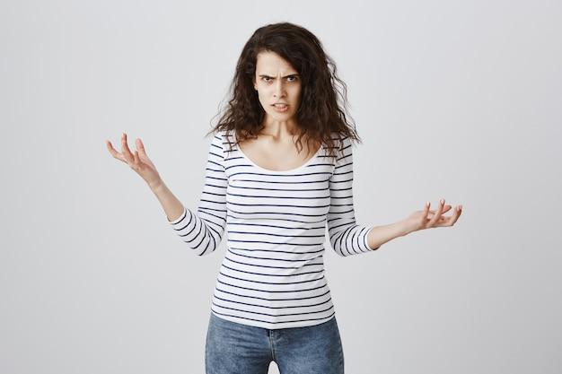 Mulher brava e irritada reclamando, apertando as mãos e franzindo a testa, angustiada
