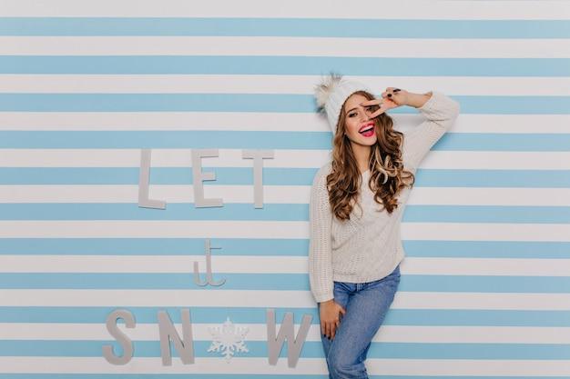 Mulher brilhante, alegre e atraente no suéter de lã quente e chapéu de malha branco está se divertindo olhando.